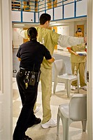 A male prisoner is searched by a female corrections officer in the Santa Ana, CA  city jail  Note day room in background