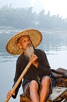 Proud Cormorant fisherman on a bamboo raft on the Li river with Karst mountain peaks China