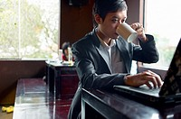 A Southeast Asian businessman works on his computer at a cafe