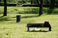 person sleeping on bench in park in rome, italy