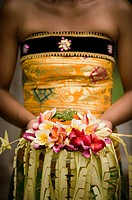A close-up of Balinese woman holding a floral arrangement