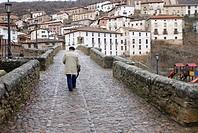 man walking over a bridge in Villoslada de Cameros, Sierra cebollera nature reserve, La Rioja, Spain