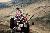 Scottish man playing the bagpipes.