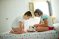 boy and girl on a bedroom reading a book, Ludiente, Castellón, Spain
