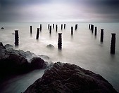 The pillars of the old pier under a grey stormy sky at Westward Ho! on the North Devon coast, England, United Kingdom