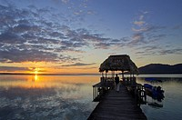 Sunset at dock in the shores of Lake Petén Itza, with Cerro Cahuí in the background, Peten, Guatemala