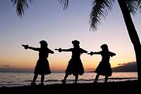 Three hula dancers at sunset at Olowalu, Maui, Hawaii
