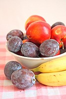 Plums and a small green apple in a white ceramic with bananas  Fresh purple plums in an white bowl  Small green apple windfall  Bananas lay beside the...