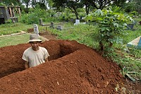 an indonesian man dig a pit in a cemetery in menteng dalam district  jakarta  indonesia  asia