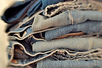 Stack of folded pairs of blue jeans  Shot with LensBaby for selective focus