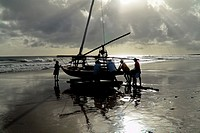 Brazilian fishermen pushing their boat manually towards the ocean during the sunrise in Uruau, state Ceara, Brazil, 16 March 2004  Fishermen use a uni...