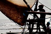 Brazilian fisherman attaching the sail to the wooden yard during the sunrise in Uruau, state Ceara, Brazil, 16 March 2004  Fishermen use a unique wood...