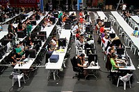 Participants of a Aviles computer party , sitting in front of computers screens and playing computers games, Asturias, Spain