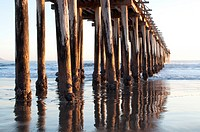 Cayucos pier pilings are reflected in the sandy water as the ocean waves come in