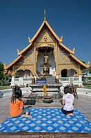 Women in prayer outside Wat Phra Singh, Chiang Mai, Thailand