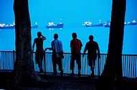 Four young men walking along promenade at twilight