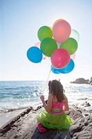 little girl sitting on rocks, holding balloons, overlooking the ocean