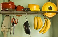 Kitchen utensils and bananas hanging from rack