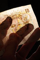 Hand houlding ten pounds note