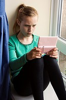 Eleven year old girl playing with a computer game