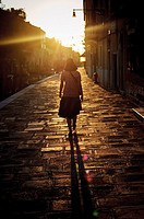 A woman wearing a hat walking in the Cannargeio during sunset time, Venice, Italy