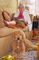 A woman relaxes in her well appointed living room with an Ipad while the dog sits on a Persian rug