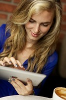 Young woman using ipad at a cafe