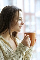 Beautiful young girl drinking hot tea while looking at the window