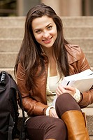 Young caucasian student smiling while holding textbooks at university library