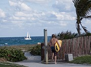 Man holding a surfboard at entrance to beach with a sailboat on the ocean in the distance.