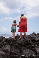 back of mother wearing a red dress, holding hands with a young girl in a striped shirt and a flower printed skirt  both are standing on giant lava roc...