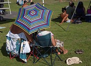 two people in camping chairs from behind in a park at a concert with a striped sun umbrella.