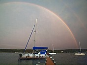 A double rainbow appears over Martha,s Vinyard, Massachusetts on a stormy day  Boats are moored in Laguna Pond, an Atlantic Ocean inlet