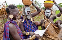 Jinka Ethiopia Africa village Lower Omo Valley Mago National Park wild tribe Mursi women with clay pots in their lips working on modern computer email...