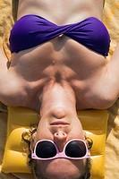 Woman sunbathing in purple bikini and pink sunglasses, lying on yellow towel  Malaga, Spain