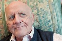 Closeup portrait of an elderly man wearing oxygen nasal tube