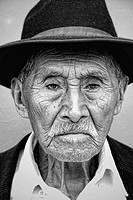 Local black and white image of old man with wrinkles and great eyes against bright wall with black cowboy hat in tourist village of Antigua Guatemala