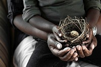 hands of black mother with child looking at nest with egg