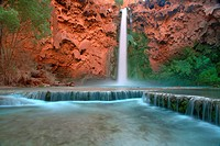 Low angle view in the Grand Canyon as Mooney Falls drop into turquoise pool, USA, Arizonal