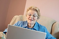 Mature woman using laptop and smiling