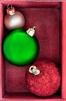Three green, red and gold Christmas baubles close up in a red wooden box.