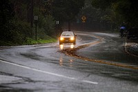 Car Driving with Headlights on in Rain Storm in hills of California near Santa Cruz