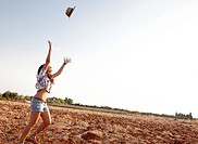 girl throwing a hat into the air