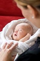 Mother holding sleeping newborn