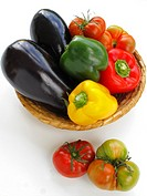 Basket with aubergines, tomatoes and peppers