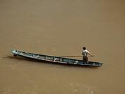 Fisherman on his boat paddling on the Mekong River in Luang Prabang Laos