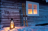 Lantern in the snow outside a cottage with skiing equipment and light in a frosty window