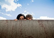 Woman and his son hiding behind a wall