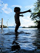 A young child splashing in a lake in New Hampshire