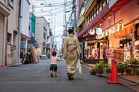 Woman with baby walking in the streets of Tokyo, Japan, Asia